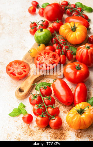 Selection of organic large heirloom and cherry tomatoes on white cream brown concrete background, selective focus - Stock Photo