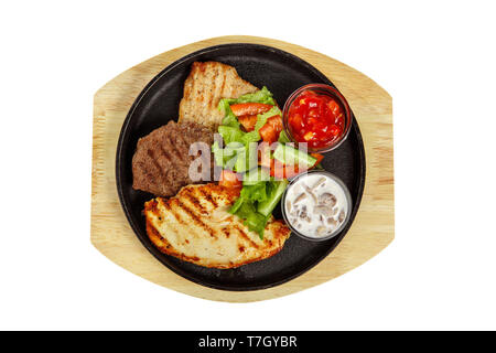 Three pieces of different types of meat with vegetable salad. Steak beef, pork, grilled meat, barbecue, on a plate with tomato, spicy, red sauce and t - Stock Photo