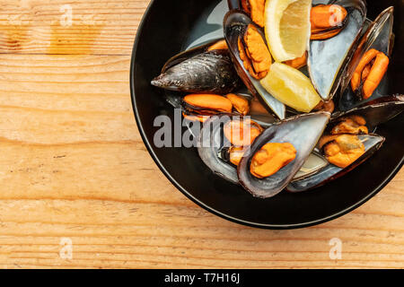 A closeup photo of boiled mussels with lemon slices, shot from the top on a wooden background with a place for text - Stock Photo
