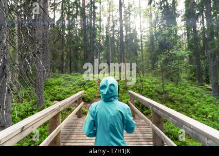 Young woman walking in boreal forest seen from behind her. - Stock Photo