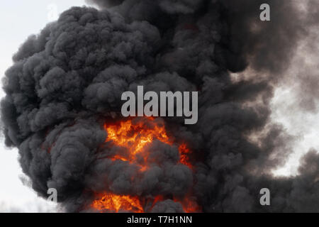 View of flames of red-orange fire and motion clouds of black smoke covered sky. Selective focus, motion blur from strong fire and high temperature fro - Stock Photo