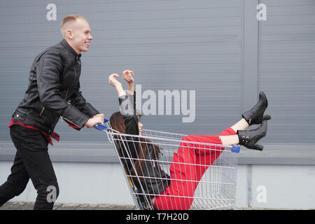 Guy rolls his attractive young girlfriend in the trolley on parking lot of the supermarket. Side view. - Stock Photo