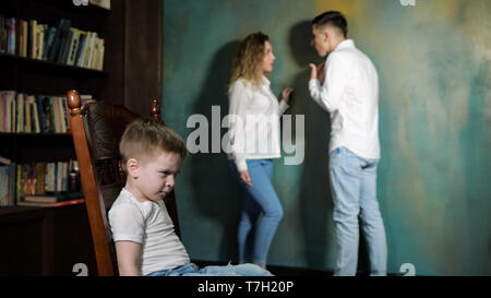 Couple of parents arguing in front of their kid. Sad little boy is listening his parent's shouting on each other, sitting on the chair, side view. - Stock Photo