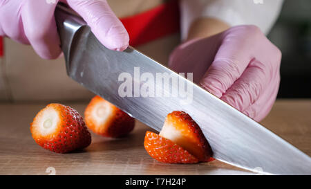 Chef woman is cutting strawberry on slices in rubber gloves on wooden table. Hands close-up.