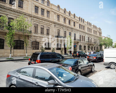 Baku, Azerbaijan - May 2, 2019: Street view of old soviet building State Border Service of the Republic of Azerbaijan with cars parked in front - Stock Photo