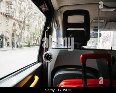 Defocused view from hackney carriage taxi cab in Baku Azerbaijan with red luggage inside and street view with people silhouette - Stock Photo