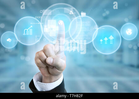 Man wearing suit pressing earth button on invisible screen  with index finger as internet concept closeup - Stock Photo