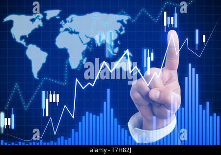Closeup of index finger touching growing graph on invisible display as statistics analysis concept with blue world map background - Stock Photo
