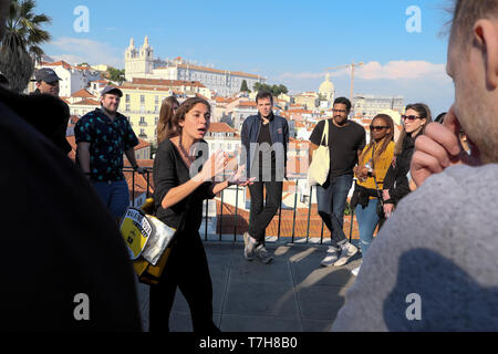 Young woman tour guide giving historical talk about Portuguese history to tourists on holiday in Alfama Lisbon Portugal Europe EU  KATHY DEWITT - Stock Photo