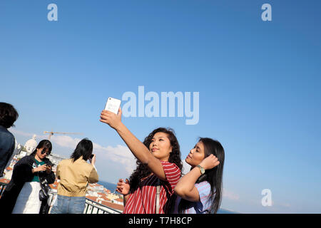 Beautiful young woman with friend taking selfie with mobile phone with background of Alfama district of Lisbon in Portugal Europe EU  KATHY DEWITT - Stock Photo