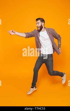 Full length portrait of a cheerful young man wearing casual clothes isolated over yellow background, running away - Stock Photo