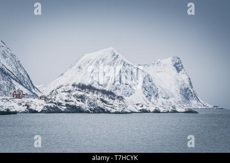 Cold winter day at Senja, Norway. Lonely houses near high snow covered mountains in dull scenery - Stock Photo