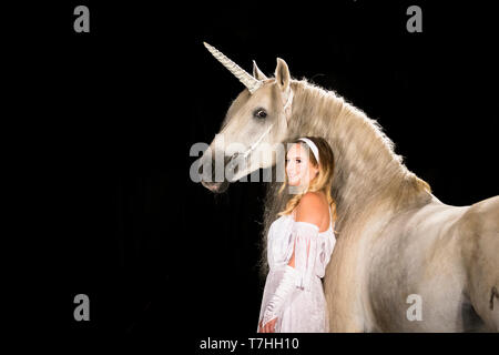 Young woman (fairy, virgin) standing next to unicorn (Pure Spanish Horse with attached horn). Germany - Stock Photo