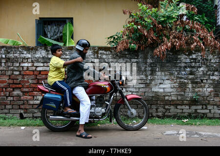 Kolkata, India - February 4, 2019 : local indian father try to starting old motorcycle to sending his child to school in the morning. indian child boy - Stock Photo