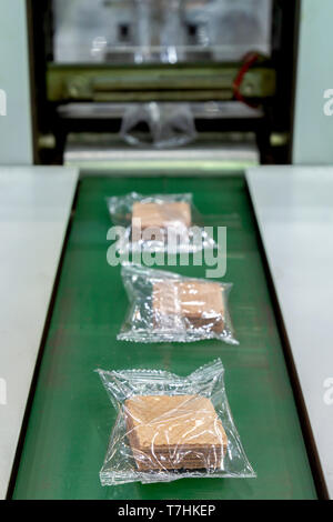crispy wafer biscuits packing in the plastic back in production line on the conveyor belt of automatic packing machine at bakery factory. food industr - Stock Photo