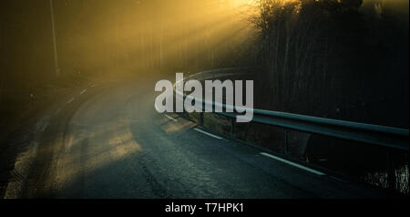 Moody fog over the road by the shores of Jonsvatnet lake. Morning orange light. Autumn in Norway. - Stock Photo