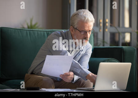 Grey haired mature man calculating bills, using laptop at home - Stock Photo