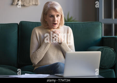 Shocked grey haired mature woman reading unexpected news on laptop - Stock Photo