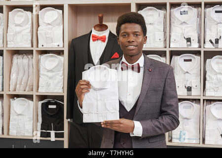Young african man holding white shirt and posing in boutique of man clothing. Man in white shirt, red bow tie, waistcoat and grey jacket looking at camera. Shelves with shirts on background. - Stock Photo