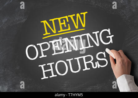 text NEW OPENING HOURS written on blackboard with hand holding piece of chalk - Stock Photo