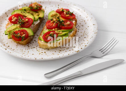 Healthy sandwiches with cream cheese avocado, tomatoes and thyme. Food on the white stylish plate. - Stock Photo