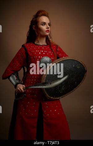 Beautiful, brave woman wearing in red medieval tunic holding shield and dagger. Serious, young woman with ginger hair looking away, posing in studio on solid background. - Stock Photo