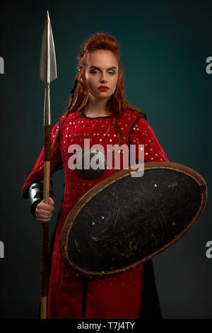 Female model looking at camera, holding spear and shield. Beautiful, brave and serious woman wearing in red medieval costume, tunic. Woman with ginger hair standing, posing in studio. - Stock Photo