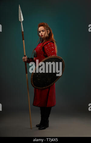 Brave female warrior with serious facial expression holding long spear and protective shield. Beautiful woman with ginger hair wearing in red medieval tunic, looking at camera, standing posing. - Stock Photo