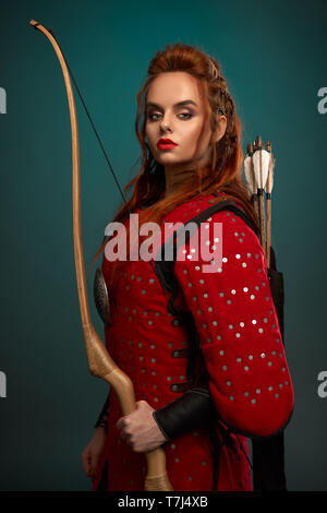 Gorgeous woman with ginger hair, red lips looking at camera, posing. Beautiful female warrior holding bow in hand, with arrows behind back, wearing in red medieval tunic. - Stock Photo