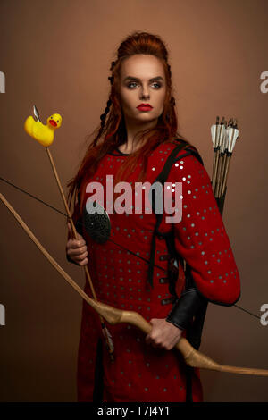 Serious, brave woman, medieval warrior holding bow and arrow with rubber duck. Gorgeous, pretty woman wearing in red tunic looking away, posing in studio. - Stock Photo