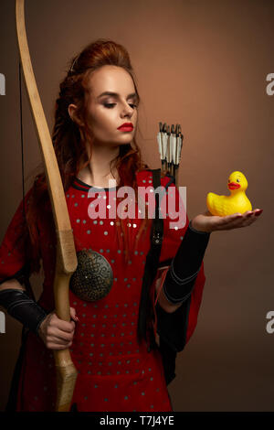 Beautiful woman warrior wearing in medieval red tunic holding small, yellow rubber duck on hand, looking at it. Serious model with red lips and ginger hair posing, holding bow. - Stock Photo