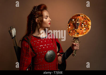 Beautiful woman wearing in medieval red tunic holding dagger with delicious pizza. Gorgeous, brave warrior with arrows behind back, red lips posing in studio. Concept of junk food. - Stock Photo