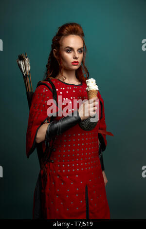 Gorgeous model with red lips and ginger hair posing, holding tasty, white ice cream. Beautiful woman warrior wearing in medieval red tunic with arrows behind back, looking away. - Stock Photo
