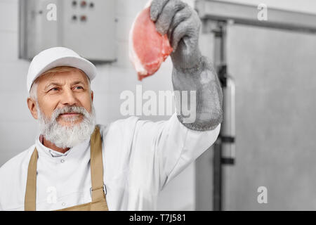 Butcher wearing in white uniform, white cap, brown apron, special gloves holding steak, checking quality. Elderly man working on meat production, modern factory. Food industry. - Stock Photo