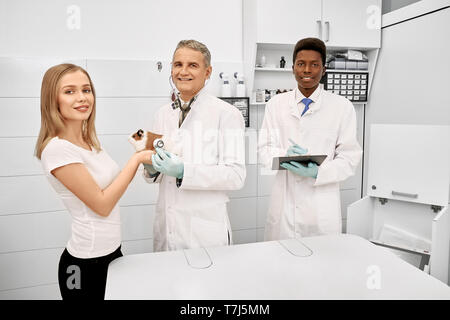 Veterinarian, african assistant with folder and owner of hamster posing together in vet clinic. Beautiful woman holding pet on examination. Doctor, specialist and woman smiling, looking at camera. - Stock Photo