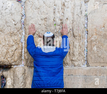 Jerusalem,Israel,27-march-2019:Jewish man prays in blue with keppel with david cross next to a crack filled with letters containing written prayers at - Stock Photo