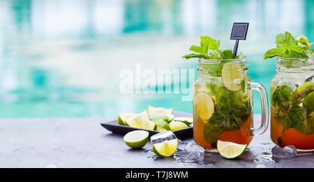 Mojito cocktail in glass jars on blue water background. Copy space. - Stock Photo