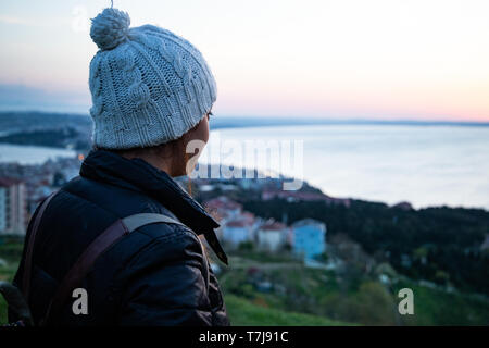 millennial girl with warm hat looking in to a sunset sea - Stock Photo