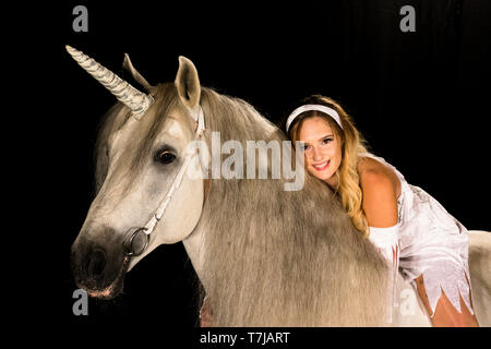 Young woman (fairy, virgin) on back of unicorn (Pure Spanish Horse with attached horn). Germany - Stock Photo