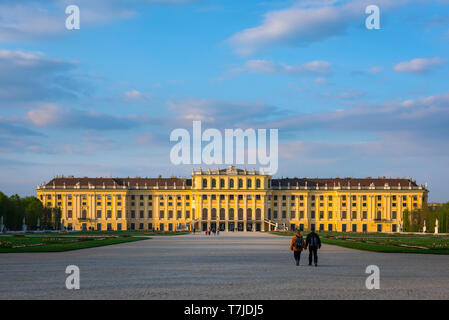 Palace Vienna, view at sunset of a middle age couple walking towards the south side of the Schloss Schönbrunn palace in Vienna, Austria. - Stock Photo