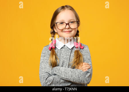 Closeup portrait of a funny little girl in glasses on a yellow background. Child schoolgirl folded her arms and looks into the camera. - Stock Photo