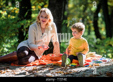 Mom and kid boy relaxing while hiking in forest. Family picnic. Mother pretty woman and little son sit on plaid relaxing forest picnic. Good day for spring picnic in nature. Explore nature together. - Stock Photo