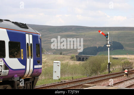 Northern train leaving at Garsdale station on Settle to Carlisle railway line passing semaphore signal on 30th April 2019, Dandry Mire viaduct in view. - Stock Photo