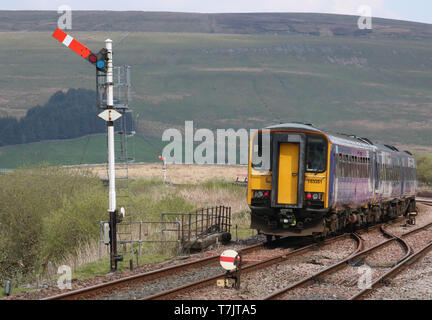 Northern train leaving at Garsdale station on the Settle to Carlisle railway line passing semaphore signal on 30th April 2019. - Stock Photo