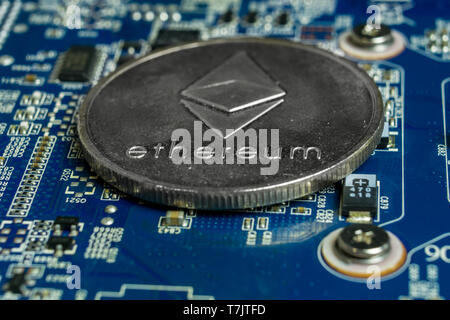 A single Ethereum coin on the blue computer motherboard - Stock Photo
