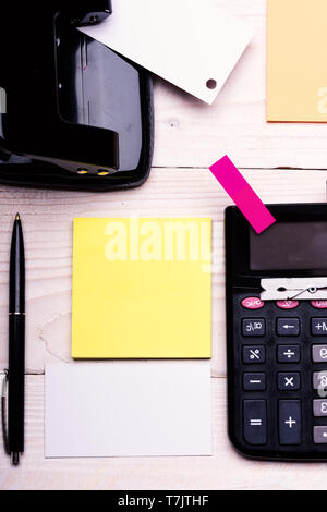 Office supplies and business idea concept. Business card with empty space and yellow sticky notes. Bookmark of pink color near pen and hole punch on white wooden background. Stationery and calculator. - Stock Photo