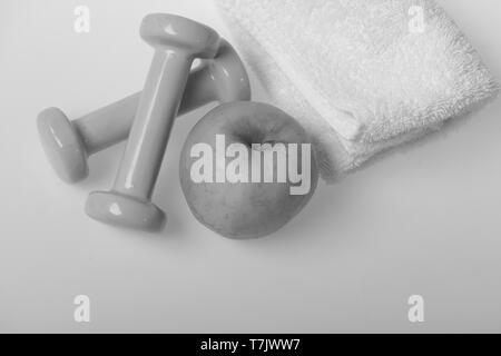 Barbells in small size next to apple fruit, top view. Dumbbells made of blue plastic near soft towel on white background. Healthy lifestyle and sports concept. Health regime and fitness symbols - Stock Photo