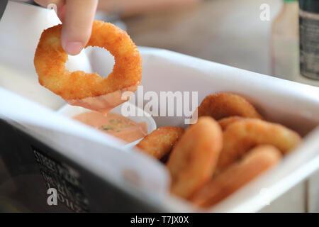 Onion rings with sauce on wooden table - Stock Photo