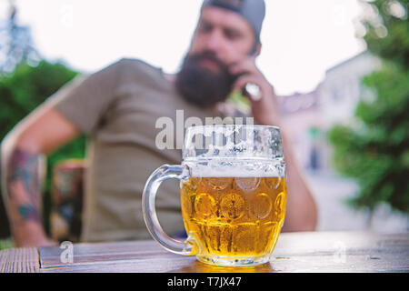 Man sit cafe terrace enjoying beer defocused. Alcohol and bar concept. Craft beer is young, urban and fashionable. Distinct beer culture. Mug cold fresh beer on table close up. Creative young brewer. - Stock Photo