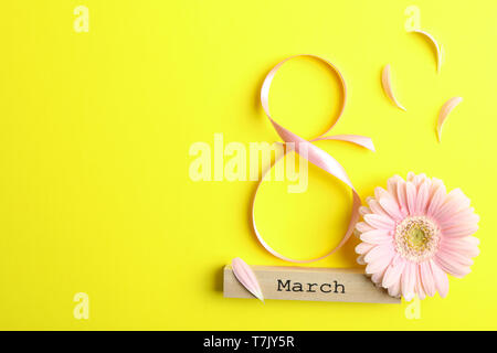 8 March, International Women's Day. Figure eight of pink ribbon with beautiful gerbera on yellow background. Space for text - Stock Photo